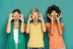 Three beautiful girls covering eyes with cucumber pieces. Three beautiful girls in colourful clothes having fun, covering eyes with cucumber pieces on green royalty free stock photos