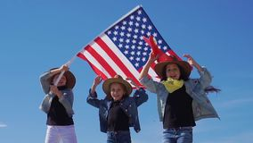 Three beautiful girls in cowboy hats with the American flag. stock video