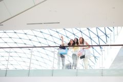 Three beautiful girls dressed in stylish casual clothes stand on the second floor of a mall under a glass roof stock photos