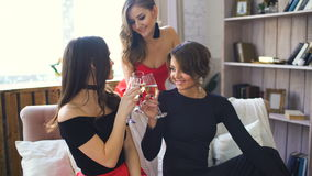 Three beautiful girls drink champagne and cheers. Women having fun laugh in bedroom stock video footage