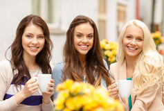Three beautiful girls drinking coffee in cafe. Holidays, food and tourism concept - three beautiful girls drinking coffee in cafe Stock Image