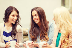 Three beautiful girls drinking coffee in cafe. Holidays, food and tourism concept - three beautiful girls drinking coffee in cafe Royalty Free Stock Photo