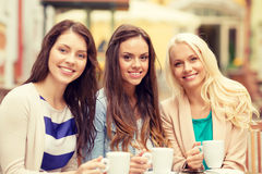 Three beautiful girls drinking coffee in cafe. Holidays, food and tourism concept - three beautiful girls drinking coffee in cafe Stock Images