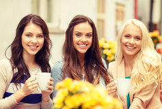 Three beautiful girls drinking coffee in cafe. Holidays, food and tourism concept - three beautiful girls drinking coffee in cafe Royalty Free Stock Photos