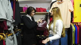 Three beautiful girls fighting over bag in shop. Friends fighting over a bag in the mall stock footage