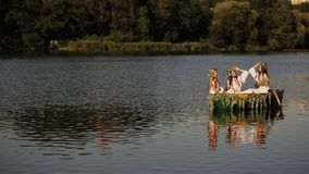 Three young girls with long hair in a boat floating on the river. Girls in Slavic costumes with a wreath on his head stock video footage