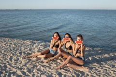 Three beautiful girls in jean shorts and black bras are sitting on the sand near the sea and holding watermelon slices stock photo