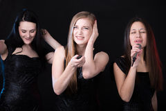 Three beautiful girls in karaoke. Focus on irritated blond girl with remote control trying to switch off song, her friends having fun, singing and dancing on Stock Photos