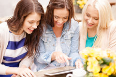 Three beautiful girls looking at tablet pc in cafe Stock Photo