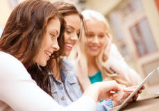 Three beautiful girls looking at tablet pc in cafe Royalty Free Stock Photos