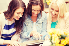 Three beautiful girls looking at tablet pc in cafe Royalty Free Stock Images