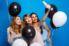 Three beautiful girls making selfie at party over blue background. Stock Photography
