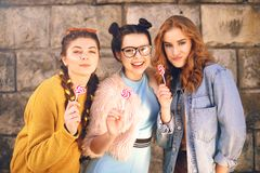 Three beautiful girls models eat lollipops. Girlfriends with different hairstyles and styles. Girls send kisses, wriggles, laugh royalty free stock photography