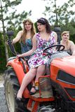 Plus size model  black bra xxl woman Young beautiful busty curv. Three beautiful girls plus size manages a tractor in a garden nursery Stock Image
