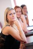 Three beautiful girls in restaurant. Three beautiful girls in a restaurant, focus is on the first one stock photo