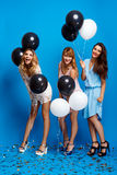 Three beautiful girls resting at party over blue background. Royalty Free Stock Photo