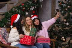 Three beautiful girls in santa hats smiles make selfies near of. Christmas tree. Three beautiful women sits a room near of Christmas decorations Royalty Free Stock Photos