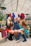 Three beautiful girls with shopping bags Stock Photos