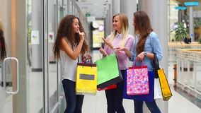 Three beautiful girls with shopping bags watch stock video footage