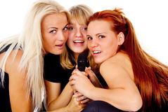 Three beautiful girls sing into the microphone. Isolated on white background Stock Photography