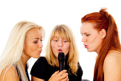 Three beautiful girls sing into the microphone. Isolated on white background Stock Photos