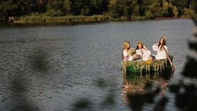 Three beautiful girls in the Slavic clothes in a boat on the river. women pass each other a bouquet of wildflowers. girl stock video footage