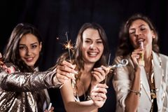 Three beautiful girls in stylish casual clothes are having fun with ribbons and pipes and sparklers on a black royalty free stock photos