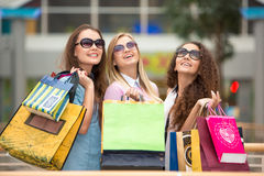 Three beautiful girls in sunglasses with shopping Royalty Free Stock Photography