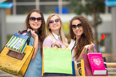 Three beautiful girls in sunglasses with shopping Royalty Free Stock Photos