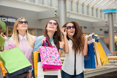 Three beautiful girls in sunglasses with shopping Stock Images