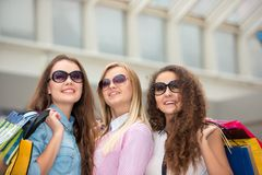 Three beautiful girls in sunglasses with shopping Royalty Free Stock Images