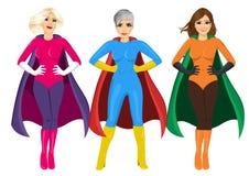 Three beautiful girls in superhero costume standing with hands on hips Stock Image