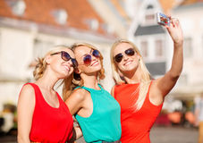 Three beautiful girls taking picture in the city Royalty Free Stock Photos