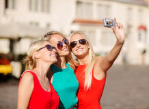 Three beautiful girls taking picture in the city Stock Images