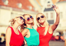 Three beautiful girls taking picture in the city Stock Photos