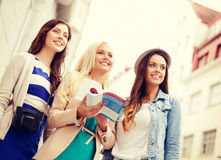 Three beautiful girls with tourist book in city Stock Photo