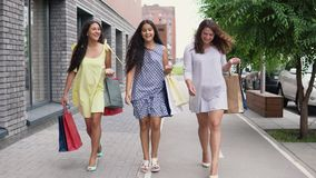 Three beautiful girls walk down the street with bags in their hands after shopping, having a good mood. 4K