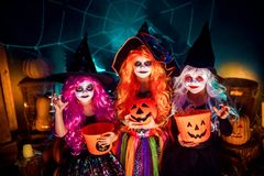 Three cute funny sisters celebrate the holiday. Jolly children in carnival costumes ready for Halloween. royalty free stock image