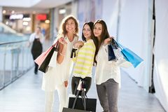 Three beautiful happy girls dressed in nice casual clothes walk with lots of shopping bags in the mall. Shopping time royalty free stock image