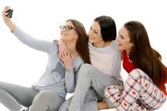 Three beautiful happy girls ih their pajamas taking selfie with stock photos