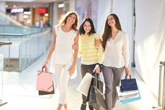 Three beautiful joyful girls dressed in nice casual clothes walk with lots of shopping bags in the mall. Shopping time stock image