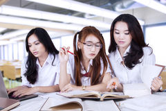 Three beautiful learners studying together in class Stock Image