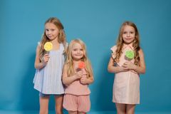 Three beautiful young girls and sweet candy lollipops stock image