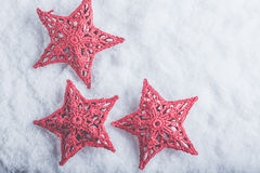 Three Beautiful magical vintage red stars on a white snow background. Winter and Christmas concept Stock Photo