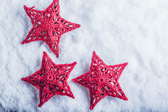 Three Beautiful magical vintage red stars on a white snow background. Winter and Christmas concept Royalty Free Stock Photography