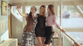 Three beautiful models doing selfie on mobile phone standing inside the ship stock video
