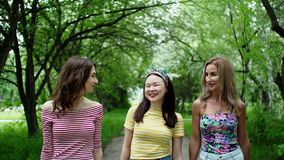 Three beautiful multi ethnic girls friends walks park smiling laughing together. stock video footage