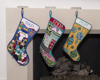 Three beautiful needlepoint stockings hanging in front of the fireplace Stock Images