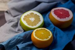 Three beautiful pieces of cut in half different citrus fruits orange grapefruit sweeties are dark blue grey kitchen towels cloth stock images