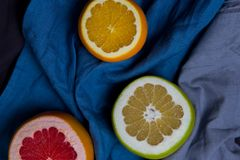 Three beautiful pieces of cut in half different citrus fruits orange grapefruit sweeties are dark blue grey kitchen towels cloth royalty free stock photo